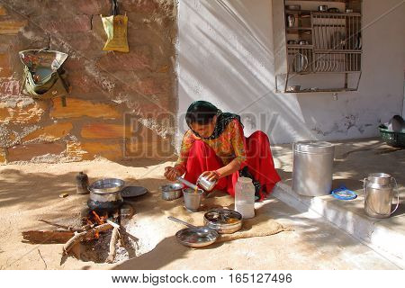 SUMRASAR, GUJARAT, INDIA - DECEMBER 19, 2013: Woman preparing thali (indian food) in the courtyard of a house in Sumrasar, local village near Bhuj