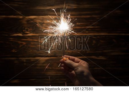 Sparklers in woman hands with wooden background
