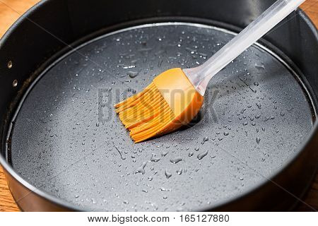 Silicon culinary brush kneading oil on baking dish. Kitchen accessory