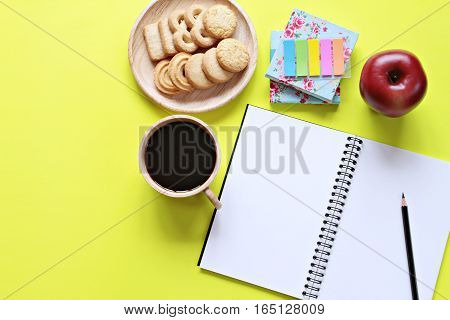 Still life, business, office supplies or education concept : Top view of working desk with blank notebook with pencil, cookies, apple, coffee cup and colorful note pad on yellow background