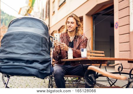 Young father with baby stroller having coffee at a cafe in Heidelberg, Germany and taking pictures of his his child.