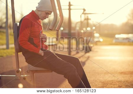 Young athlete sitting in an outdoor gym after a hard workout