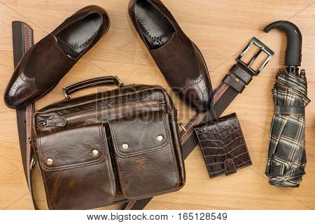 Classic brown suede shoes briefcase belt and umbrella on the wooden floor can be used as background
