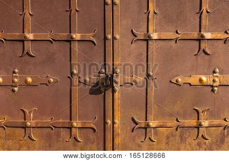 Old metal rusty door. Medieval style. sunny