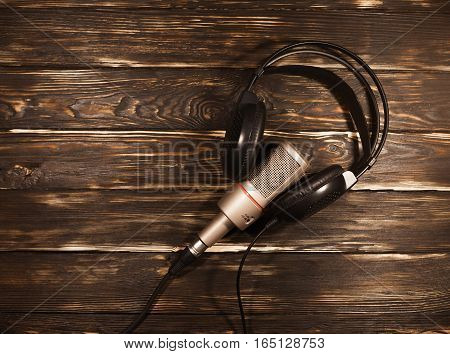 Black headphones with microphone on wooden background.