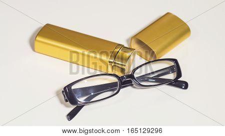 An elegant black glasses and gold case for them. White isolate.