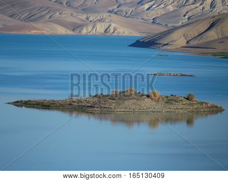 Island on artificial lake in mountainside northern countryside in Middle Atlas Mountains landscape in MOROCCO at warm sunny winter day, AL WAHDA, AFRICA, FEBRUARY.