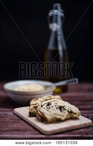 The hummus on a bread, olive in background.