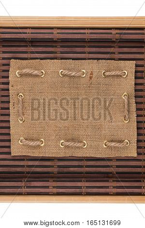 Frame made of burlap lying on a bamboo mat in the form of manuscript isolated on white background