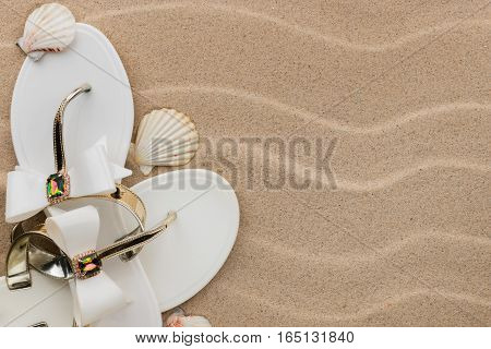 White flip-flops with rhinestones and seashell on the wavy sand. With place for your text