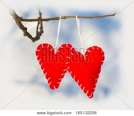 Red romantic heart hanged on a snowy forest shrub winter Valentine's Day holiday card