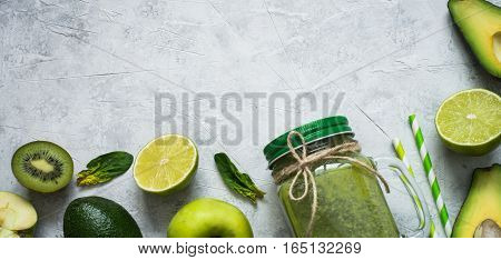 Healthy green smoothie in mason jar and ingredients. Superfoods detox diet healthy food. Green food background. Long banner format.