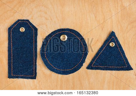 Price tags made of jeans lying on the wooden background