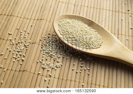Organic natural sesame seeds on wooden spoon and bamboo napkin.