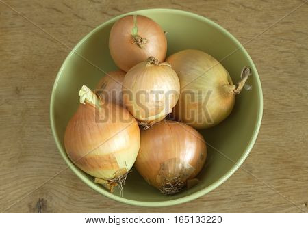 Ripe onions lies in green bowl on wooden surface top view close-up