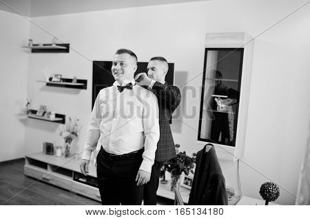 Best Man Helping Wear Groom On His Wedding Day. Black And White Photo