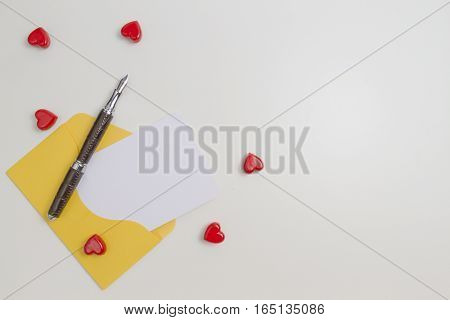 Yellow envelope, message, pen and small red hearts on white table. Top view. Copy space for text. Love letter, valentines day concept