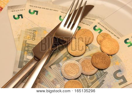 Paper and metal money with knife and fork on the plate