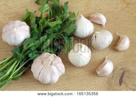 Ripe garlic and fresh green parsley on a wooden cutting board closeup
