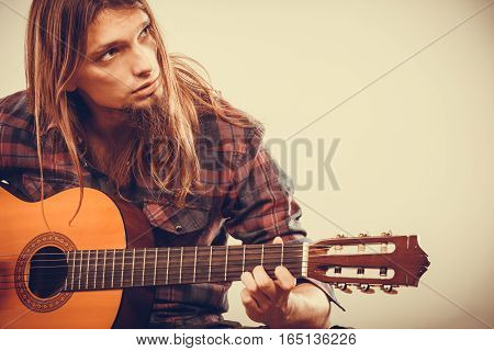 Young long haired guy playing guitar. Focused man practicing the game on the instrument.