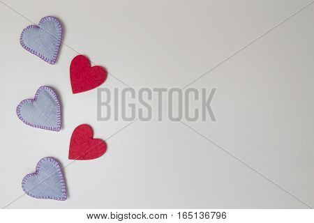 Valentine hearts of jeans denim and red felt arranged as background. Top view. Copy space for text.