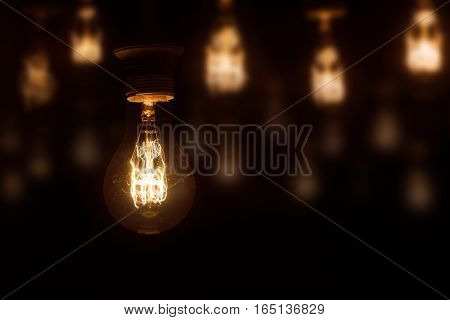 lighted vintage incandescent bulb on dark orange blurred background