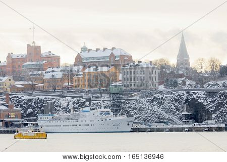 STOCKHOLM - JAN 08 2017: Passenger ferry in the harbor Stadsgarden and old buildings in central Stockholm a cold winter morning ice on the sea. January 08 2017 in Stockholm Sweden
