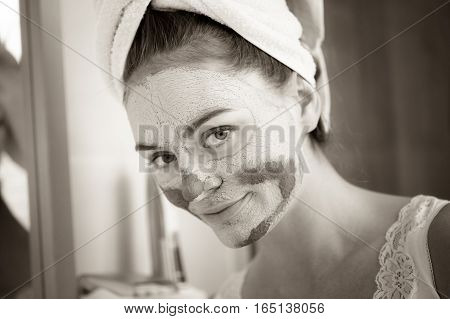 Woman in bathroom with green clay mud mask on face. Girl taking care of oily complexion. Beauty treatment.