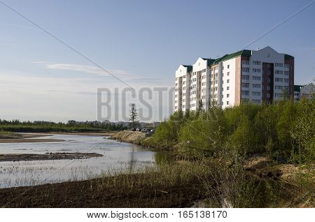 Modern multistage building situated on the bank of the river