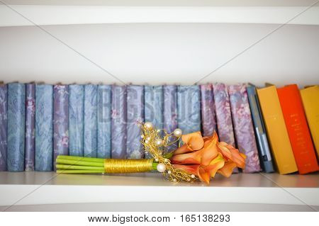 bouquet orange calla lilies on the background of colorful books on white shelf