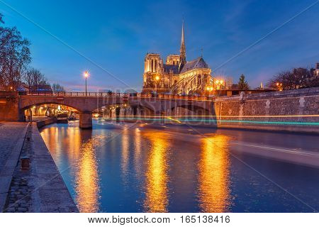 Cathedral of Notre Dame de Paris and bridge Pont de l'Archeveche, Archbishop's Bridge, as seen from Quai de la Tournelle during evening blue hour, Paris, France