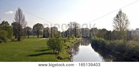 fresh spring meadow with isolated trees and Odra river in CHKO Poodri near Jistebnik city only few km from Ostrava