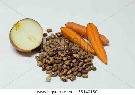 Onion cut in half Carrot and brown yellow beans isolated on white background. Healty food.