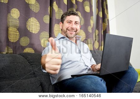 Thumbs Up Man With Laptop On Sofa