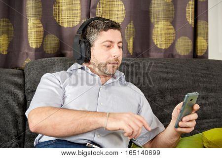 Man Listening To Music On Sofa