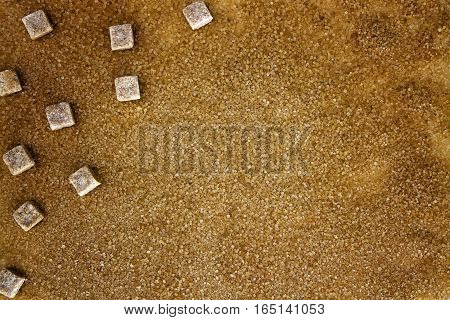 Brown sugar cubes on powdered crystal sugar background. Top view. Close up