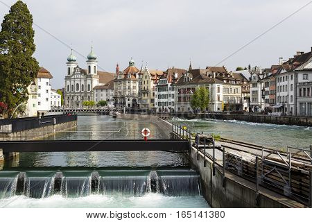 LUCERNE SWITZERLAND - MAY 02 2016: The weir in the side stream of the river Reuss together with Jesuit church and other buildings creates landscape of this attractive tourist destination.