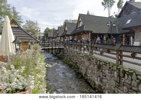 ZAKOPANE POLAND - SEPTEMBER 23 2016: Commercial pavilions that are called Goralskie Sukiennice was built in 2006 and are located by the stream and offers regional souvenirs