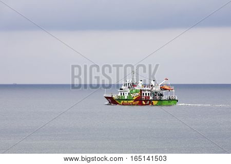 KOLOBRZEG POLAND - JUNE 21 2016: Fishing boat named Monika III is at the Baltic sea and is during a tourist cruise. This is seen from the beach in Kolobrzeg.