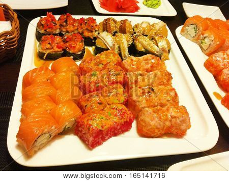 Set of rolls sushi maki salmon fish, eel, avocado with soy sauce wasabi and ginger served on white plate wooden table background Traditional Asian cuisine food served at Japanese restaurant