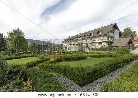 ZAKOPANE POLAND - SEPTEMBER 23 2016: Hotel Wersal that is located in a modern building with architecture reminiscent of the style of the region is surrounded by a beautiful garden providing peace