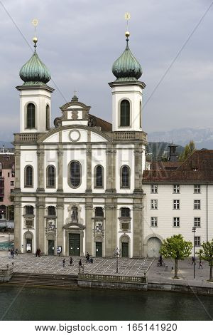 LUCERNE SWITZERLAND - MAY 02 2016: Front facade of Jesuit Church located by the Reuss river in old town. This church is one of the most visited tourist attractions in the city
