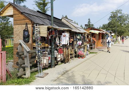 ZAKOPANE POLAND - SEPTEMBER 12 2016: Stalls in which variety of souvenirs are put on sale. These stands are made of wood as provisional and are set along the sidewalk