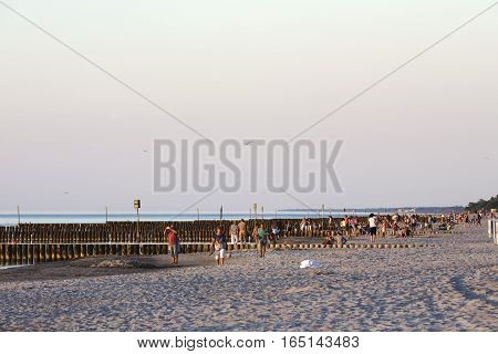 KOLOBRZEG POLAND - JUNE 24 2016: Vacationers enjoy nice evening on the sandy beach and they are walking along the coast of the Baltic Sea or they sit on the sand