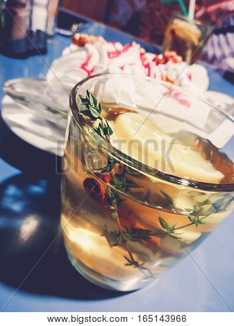 The glass cup of hot winter drink with apple, lemon