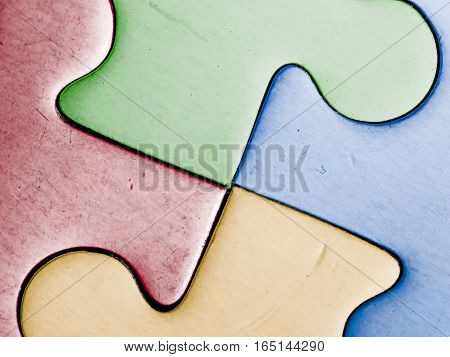close up of four colored jigsaw pieces. teamwork. solidarity human hope