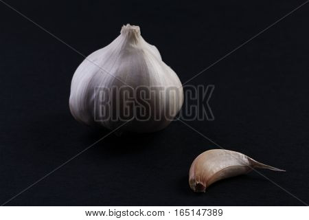 The garlic and his small part on black background