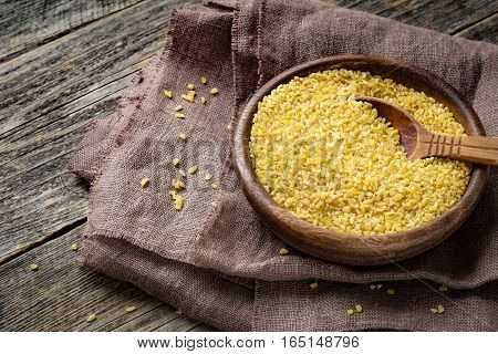 Uncooked bulgur in wooden bowl on wooden table background, rustic style. Bulgur wheat grains