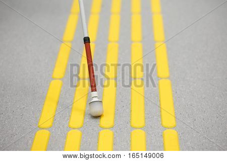 Blind pedestrian walking and detecting markings on tactile paving with textured ground surface indicators for blind and visually impaired. Blindness aid visual impairment independent life concept.