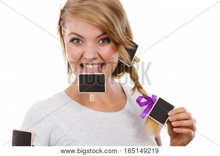 Teenage girl biting little school blackboards. Studio shot on white background.
